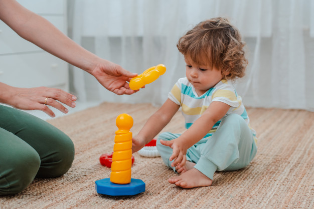 mother-child-play-floor-nursery-mom-little-baby-boy-are-doing-with-plastic-colorful-toys_73683-1063